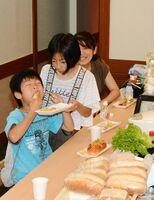 ボリューム満点のサンドイッチにかぶりつき、食事を楽しむ子どもたち=佐賀市愛敬町の「味処肴家」