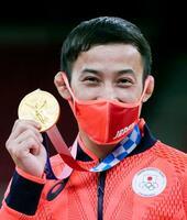 男子60キロ級で優勝し、メダルを手に笑顔を見せる高藤直寿。日本選手団初の金メダル獲得となった=日本武道館