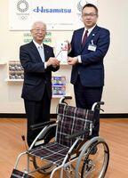 車いすを贈った矢野栄久光製薬総務部長(右)と小原健史BFTC会長=鳥栖市の久光製薬九州本社