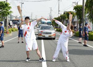 トーチキスでポーズを決める聖火ランナーの佐藤宇さん(左)と平山純子さん=10日午前、三養基郡基山町