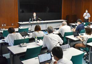 佐賀県内の新型コロナウイルスの感染状況について説明する井田政和県健康増進課長(中央奥)=16日午後、県庁