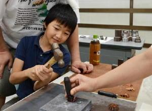 銅板を型に打ち付けて昆虫の体の丸まりをつける子ども=佐賀市のポリテクセンター佐賀