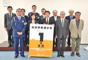 交通事故減少率ベスト1を記念し、県の古賀千加子県民環境部副部長(手前左から2人目)から松田一也基山町長(同3人目)へ表彰状とタペストリーが贈られた=基山町役場