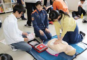 救急隊員の指導を受けながら心臓マッサージの実技に挑む生徒ら=佐賀市の九州国際高等学園