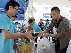 100種類以上のワインや佐賀の日本酒などを飲み比べる来場者たち=佐賀市呉服元町の656広場