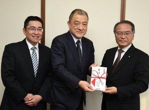 多良正裕町長(右)に寄付金を手渡す堤浩一社長(中央)と島崎健管理本部長=吉野ヶ里町役場