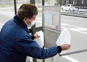 路線バス再編のお知らせを時刻表板に入れる昭和自動車の社員=佐賀市富士町の富士小学校前バス停