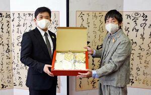 武広勇平町長にマスクを手渡すEBI江口魚の江口紘基社長(右)=上峰町役場