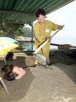 観光客に砂を掛ける桃山浩美さん=別府市上人ケ浜町の別府海浜砂湯、撮影・椎原新二