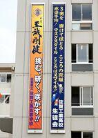 校舎北側に掲げられた新型コロナに関する懸垂幕(右)=佐賀市の佐賀工高