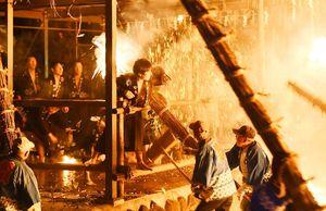 打ち付けられるたいまつの炎や火の粉に耐える男衆=伊万里市二里町の神原八幡宮