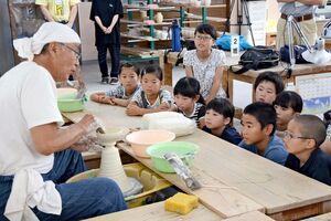矢鋪與左衛門さんからろくろの成形を学ぶ児童たち=有田町のろくろ座