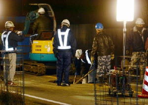 陥没した県道武雄―多久線の路面で復旧工事を行う作業員ら=武雄市北方町大崎、11日午後8時25分ごろ