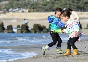 波打ち際で、はしゃぐ子どもたち=唐津市浜玉町の浜崎海岸
