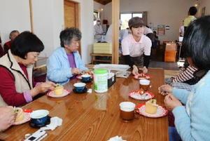 仮設住宅の集会所に開いたカフェで住民にケーキを提供する佐賀農業高食品科学科2年の生徒ら(写真奥)=熊本県菊池郡大津町室地区