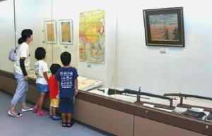 小城市民と戦争との関わりを示す展示品を見る家族連れ=小城市立歴史資料館