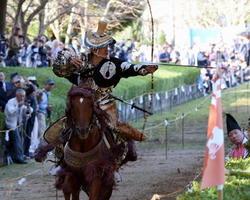 大勢の見物客が見守る中、疾走する馬上から矢が放たれる=10月29日、武雄市山内町の黒髪神社