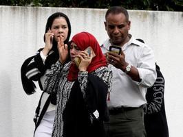 15日、ニュージーランド・クライストチャーチのモスクの外に立つ人たち(AP=共同)