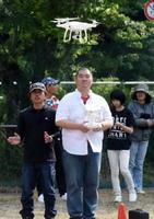 九州ドローン推進協会のメンバーの手ほどきでドローンの操縦を体験する参加者=伊万里市の旧波多津小学校跡地グラウンド
