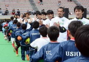 小学生向けサッカー教室終了後、ハイタッチをする山口素弘さん(右)ら元日本代表らでつくる「J-DREAMS」のメンバー