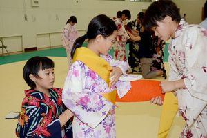 協力して浴衣の着付けをする生徒たち=有田町の有田中