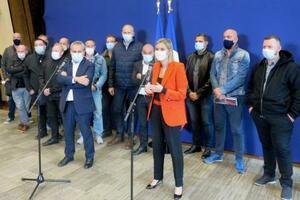ブリヂストンのベチューン工場閉鎖問題で記者会見するフランスのパニエリュナシェ産業担当相(前列右)。後列は従業員ら=19日、パリ(共同)