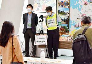 羽田からの到着客の体温をサーモグラフィーで測定する県職員=佐賀市川副町の佐賀空港