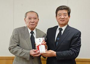 末安伸之町長に寄付金を贈った石丸食肉産業の石丸博清会長(左)=みやき町役場