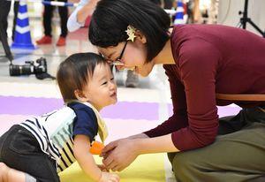 「頑張ったね」。ゴールで待っていた母親に迎えられる赤ちゃん=佐賀市のゆめタウン佐賀