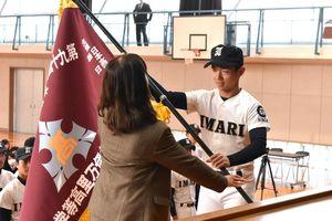 犬塚加代子校長(左)から入場行進で掲げる「選抜旗」を受け取る犬塚晃海主将=伊万里市の伊万里高校
