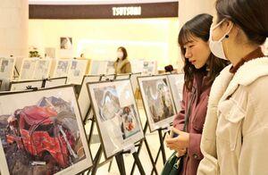 東日本大震災の被災地の当時や復興の様子をまとめたパネルを見る買い物客=佐賀市のゆめタウン佐賀