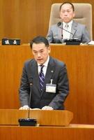 副市長選任案の見送りで緊急質問に答える峰達郎市長。後方は田中秀和議長=唐津市議会