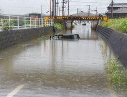 大雨で道路が冠水し、水没した車両。運転者は警察に救助された=29日午前9時20分ごろ、鳥栖市儀徳町の県道中原鳥栖線
