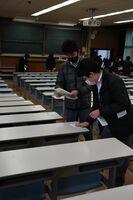試験室の机に張る受験番号を確認する担当者=佐賀市の佐賀大学本庄キャンパス