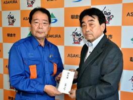 森田俊介朝倉市長(左)に見舞金を渡した松田一也基山町長=福岡県の朝倉市役所