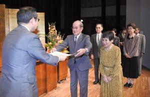 中尾清一郎佐賀新聞社社長(左)から、結婚50年を祝う表彰状を受ける金婚さん夫婦=武雄市文化会館