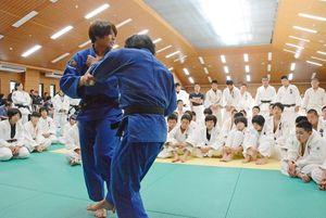 県内で柔道をする小中高の学生に技をかけるポイントを解説するコマツ女子柔道部の部員=佐賀市の総合体育館柔道場