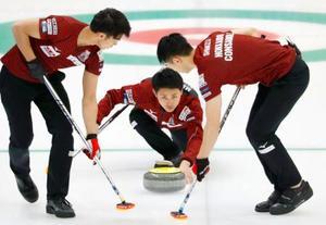 決勝のチーム東京戦で、ショットを放つコンサドーレ・松村(中央)=どうぎんカーリングスタジアム