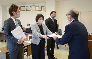 水田強会長(右)から記念品を受け取る研修生の川浪亮さん、知子さん夫妻(左の2人)と山本洋司さん=佐賀市富士支所