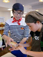 出来上がったサバサンドをワックスペーパーで包むマロンちゃん(左)と参加者=唐津市海岸通の水産会館