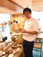 美濃焼の文化を意識したまちづくりを進めてきた小口英二さん。「カフェ温土」では若手作家の作品を展示販売している=岐阜県多治見市