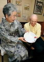 結婚当時に買った焼き物の中で、ただ一つ残っている鉢を眺める西エイ子さん(左)と守彦さん=伊万里市の自宅