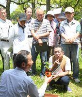 造園のプロ、相良善次さん(手前左)がゴーヤーの苗を植え込む様子を見つめる参加者ら=県立森林公園