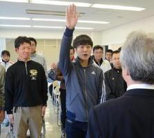 「一丸となって一つでもいい順位を狙う」と選手宣誓する松本一城さん(中央)=鹿島市陸上競技場