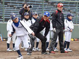真剣に走塁練習をする子どもの姿に笑顔を見せる西武ライオンズ監督の辻発彦さん(中央)=佐賀市のみどりの森県営球場