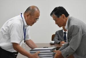 埋蔵文化財センターに関する署名と要望書を受け取る秀島市長(左)=佐賀市役所