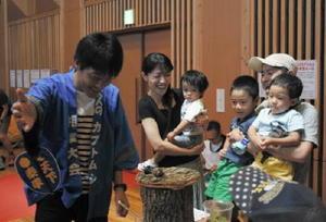 木の土俵上で繰り広げられるカブトムシたちの熱い戦いを見守る家族連れ=佐賀市富士町のフォレスタふじ