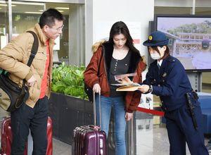 「白タク」を利用しないように呼び掛けるチラシを配る警察官(右)=佐賀市川副町の佐賀空港