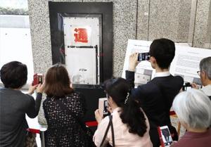 東京都庁で公開された路上芸術家バンクシーの作品に似たネズミの絵を写真に収める人たち=25日午前