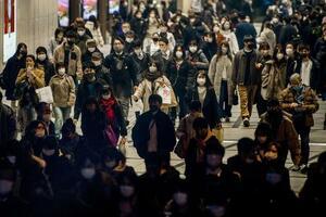 大阪・梅田をマスク姿で歩く人たち=14日
